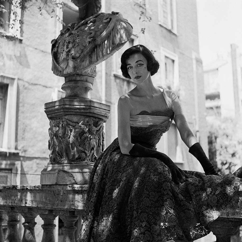 Model Dorian Leigh posing next to an antique sculpture.