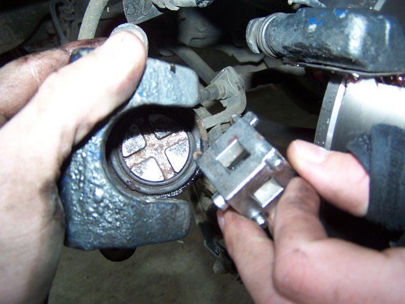 Person compressing the brake piston.