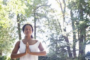 Meditating woman with trees in background.