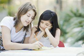 teenage girl tutoring elementary student