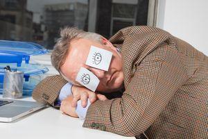 Man sleeping at desk with post-it notes drawn as eyes