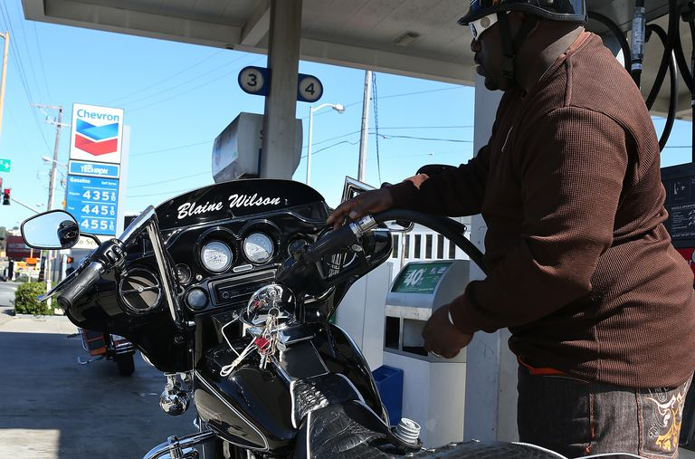 Rider filling a motorcycle at a gas station