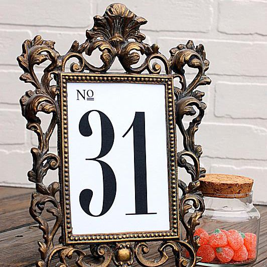 A black and white wedding table number in a frame