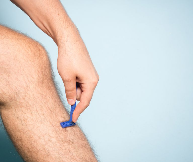 Man putting a razor to his leg like he's pretending to shave