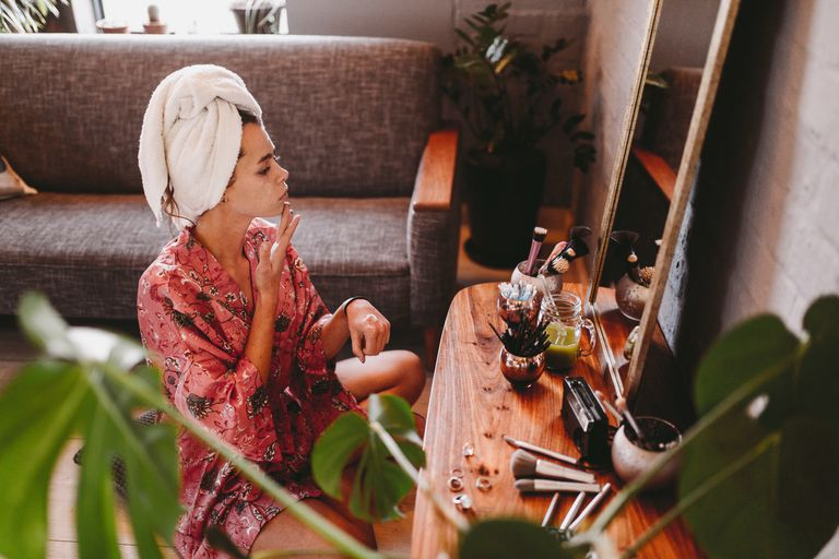Woman applying facial mask while at home sitting in front of the mirror