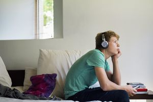 Teenage boy listening to music on a mobile phone