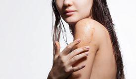 Woman applying body scrub to shoulder