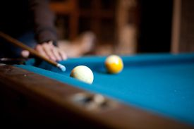 Close up, angled view of a man playing pool.
