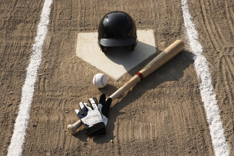 Baseball, bat, batting gloves and baseball helmet at home plate