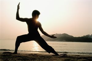 Man silhouetted by the sun during Kung Fu practice on a beach