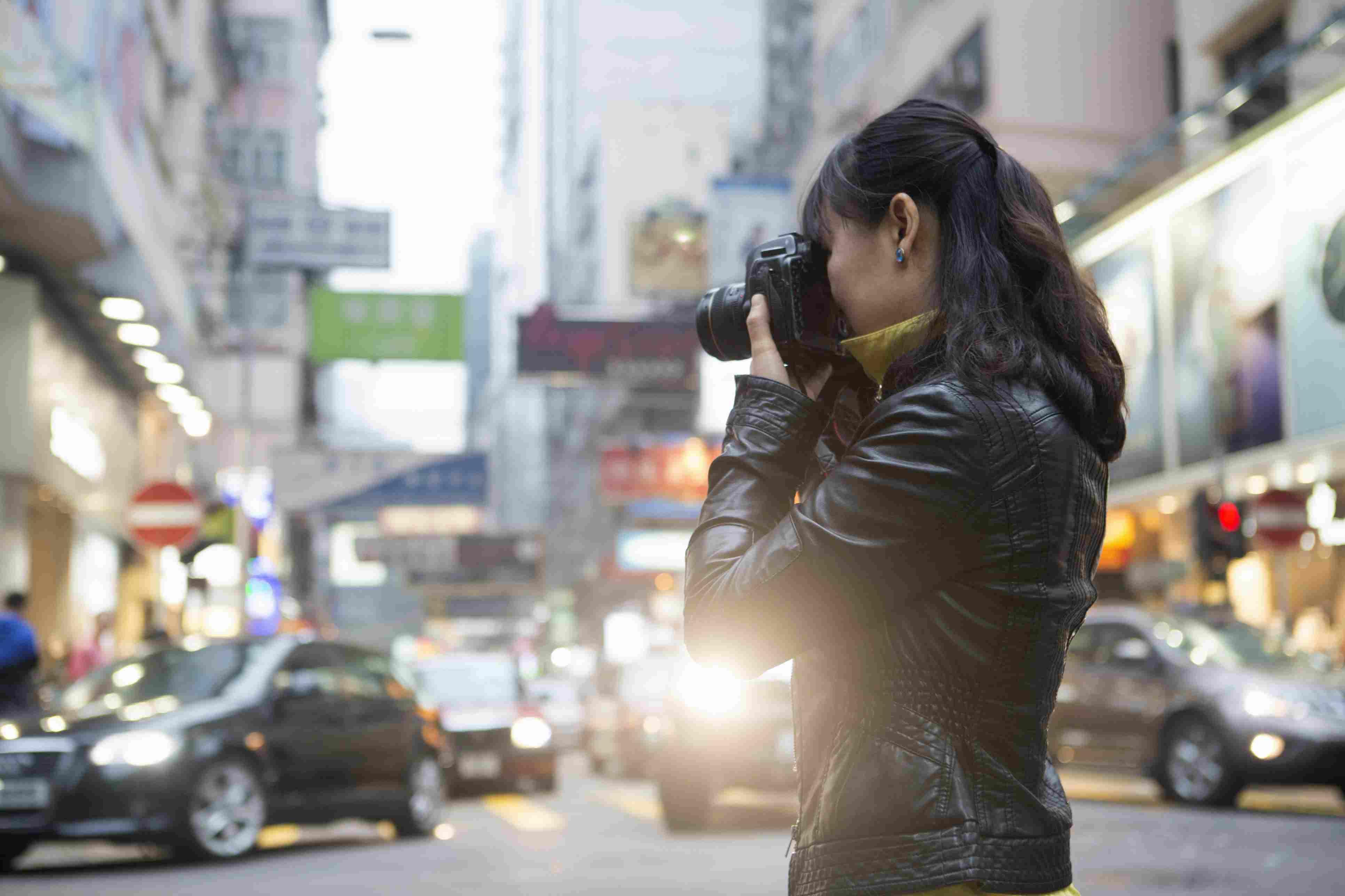 Portrait of woman using digital camera