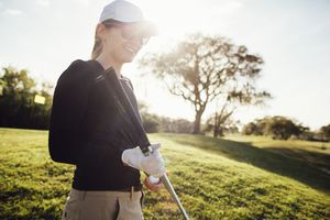 Woman holding golf clubs of different shaft lengths