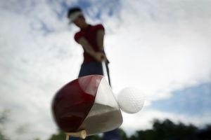 driver hitting golf ball