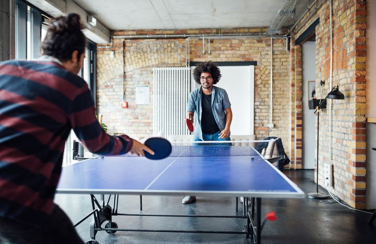 Businessman playing table tennis with colleague