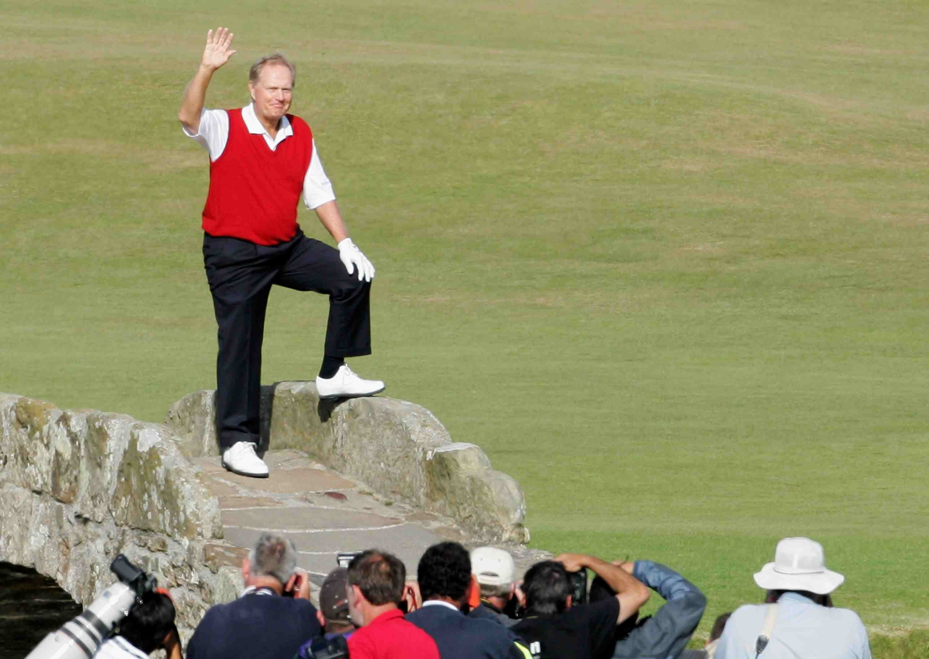 A throng of photographers snaps as Jack Nicklaus waves from the Swilcan Bridge in 2005.