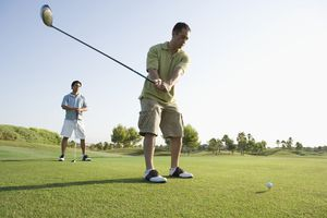 Two men tee off in golf