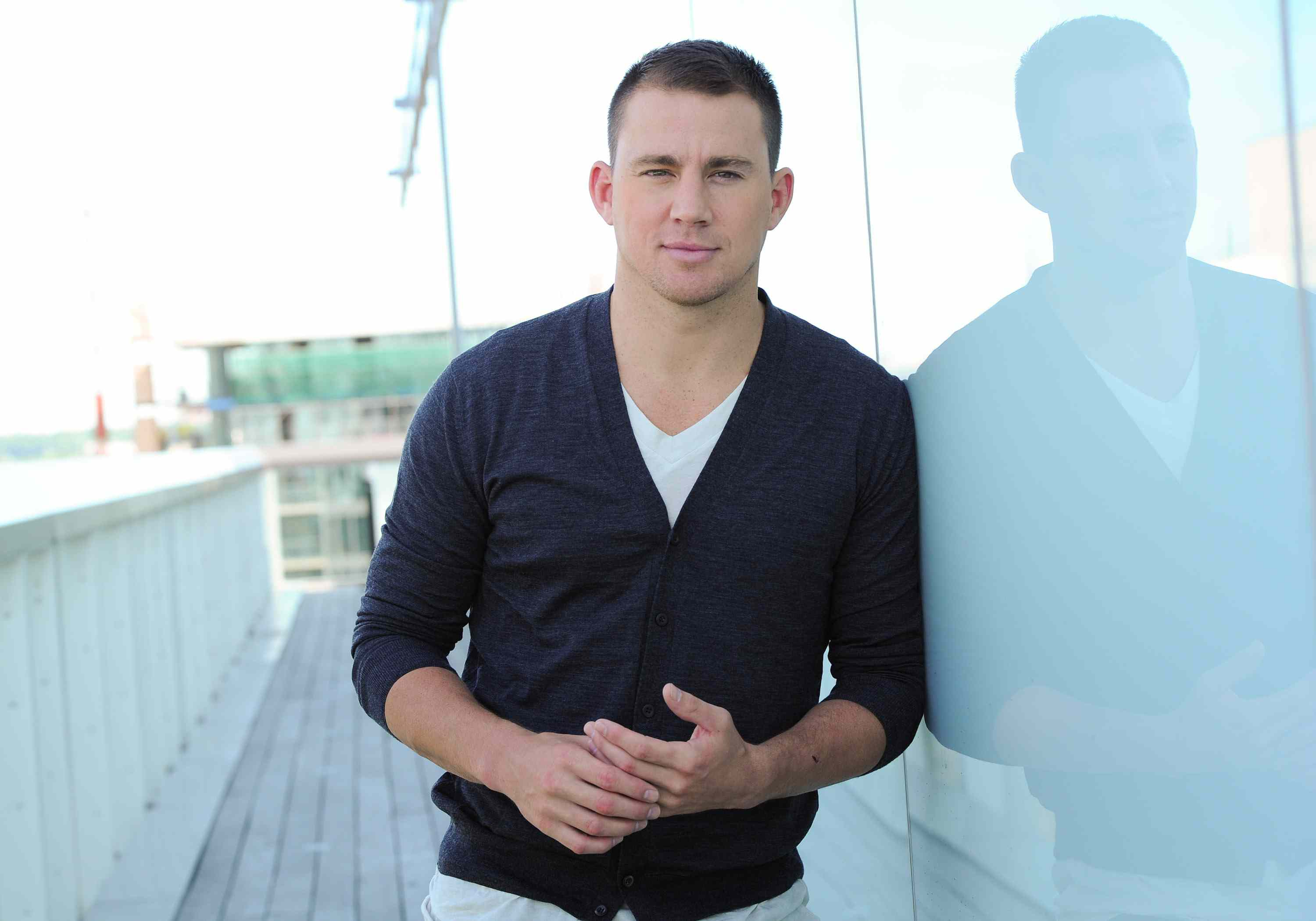 Channing Tatum leaning against a white wall outside