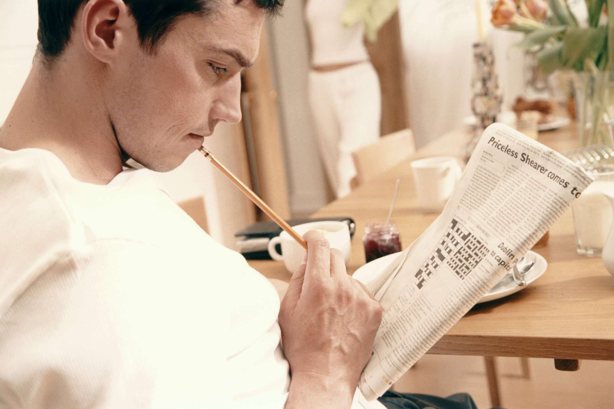Man working on a newspaper crossword at home