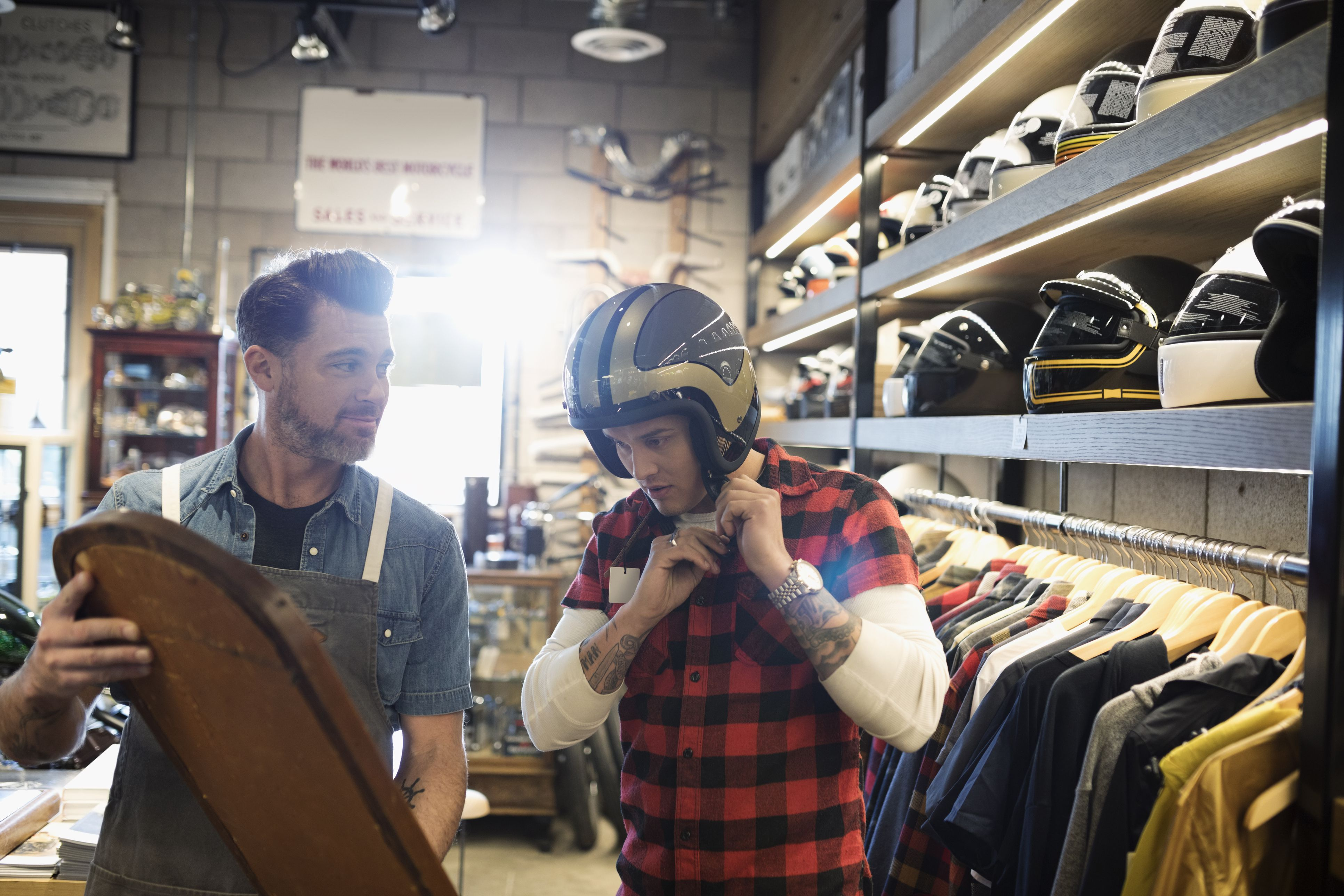 Motorcycle shop owner holding mirror for customer trying on helmet