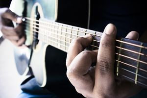 close up of fingers on a guitar fret board