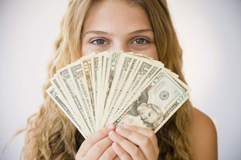 Woman holding money fan against her face