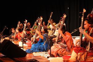 Group of people playing sitar while sitting on a stage.