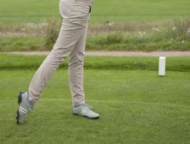 Golfer tees off from the white tees in a Red, White and Blue golf tournament.