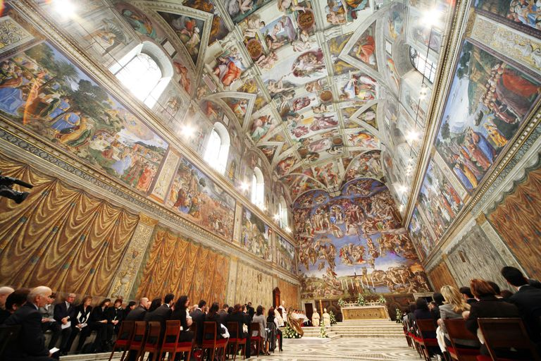 People sitting inside the sistine chapel.