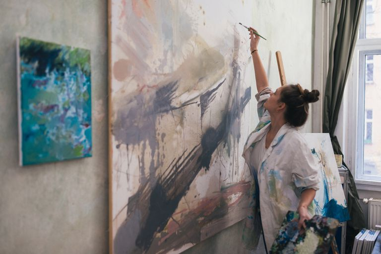 Woman painting a big work in studio.