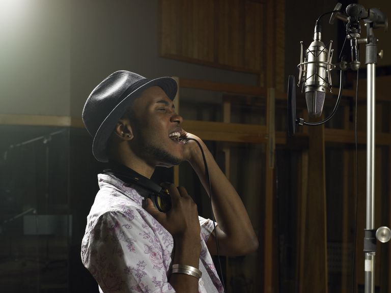 Young man singing into a mic in a studio
