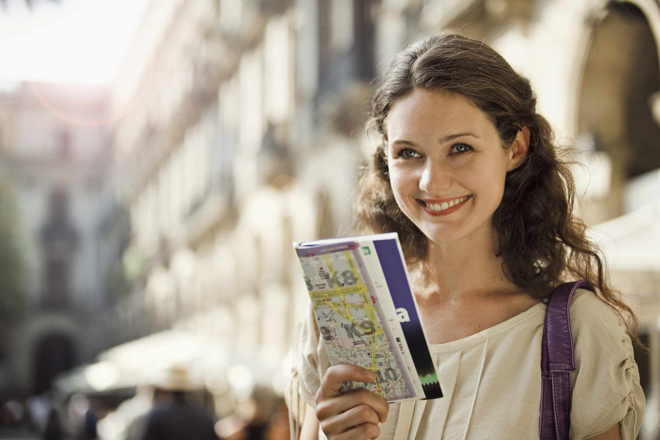 A woman holding a travel brochure and map