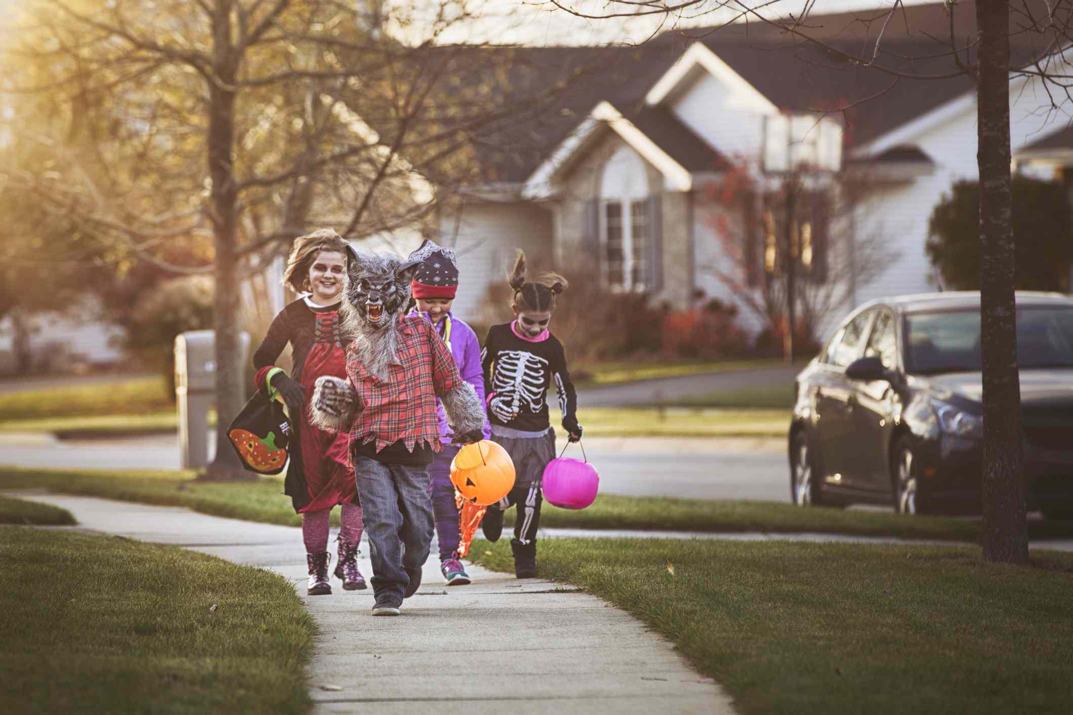 Children dressed in costumes walking on the sidewalk