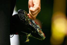 A golfer scrapes the grass off his cleats, which are designed to grip the ground to prevent slips during a swing