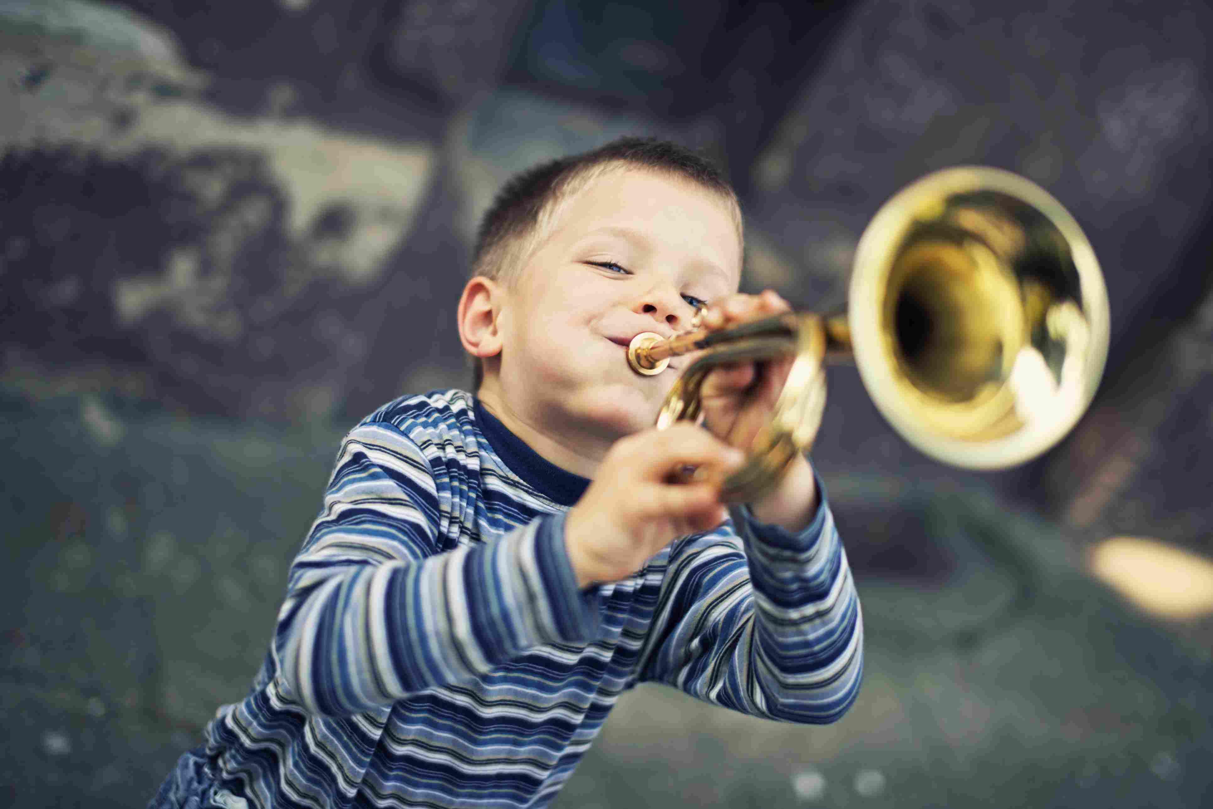 Happy little boy playing trumpet