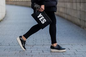 Woman in black jeans with YES purse