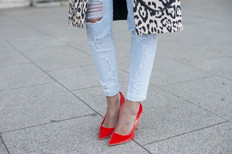 Close-up of red pumps worn with skinny jeans