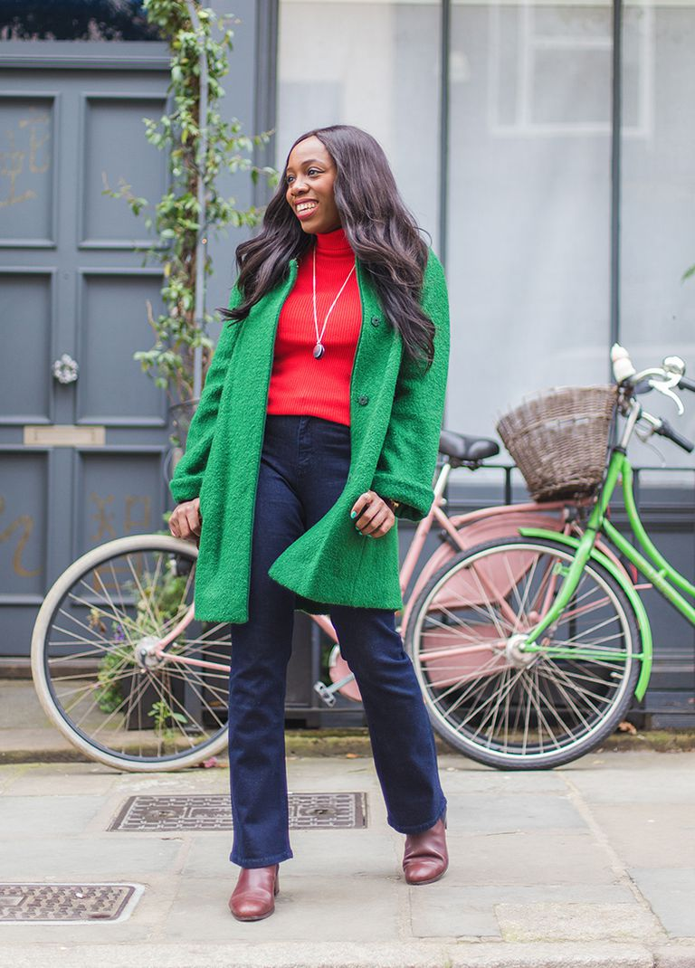 Woman wearing bootcut jeans and green coat