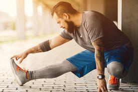 A chubby man gears up for a run.