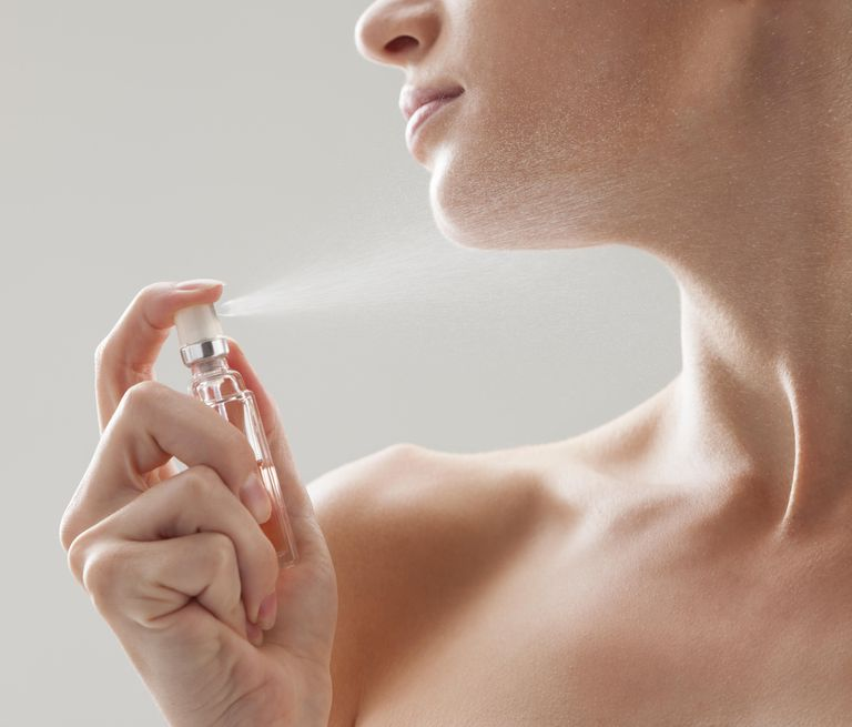 Beautiful woman spraying perfume on her neck