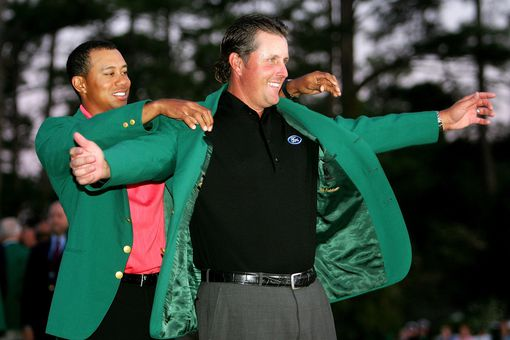 Tiger Woods puts the green jacket on Phil Mickelson after he won The Masters at the Augusta National Golf Club after the final round on April 9, 2006 in Augusta, Georgia. Mickelson won with the score seven under.