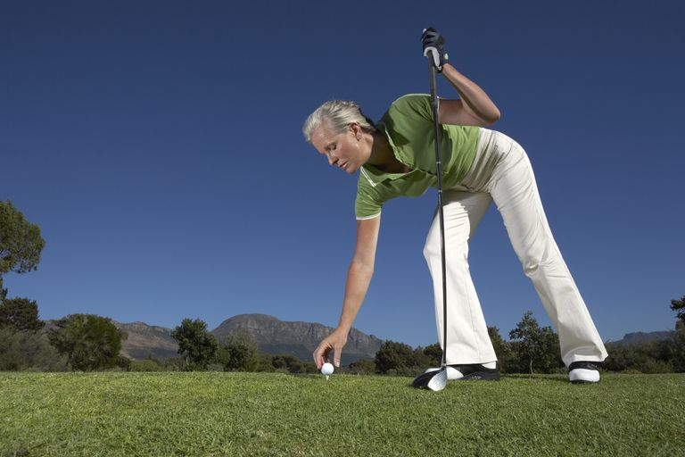 Woman placing golf ball onto tee