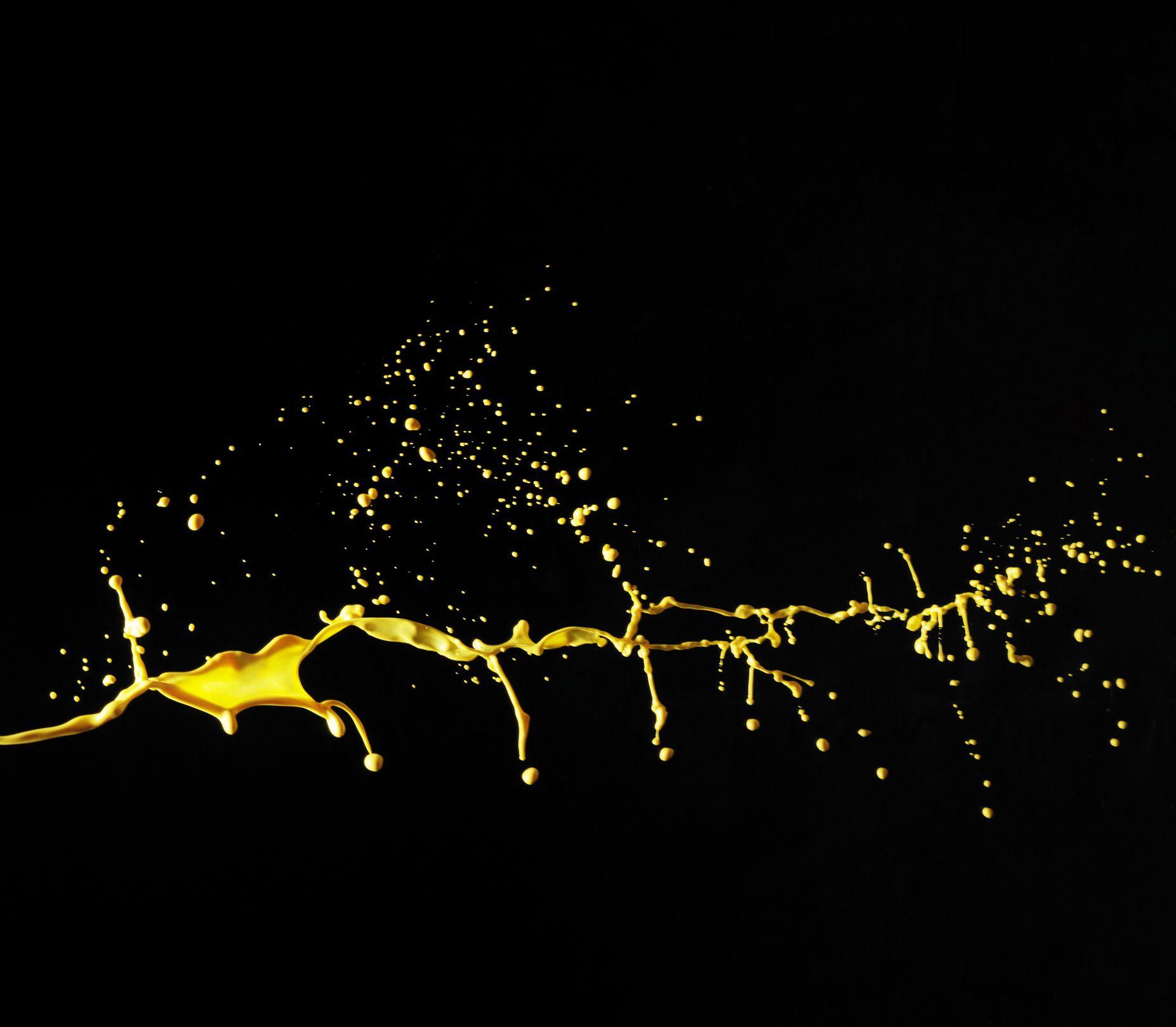 Yellow color splash on black paint canvas