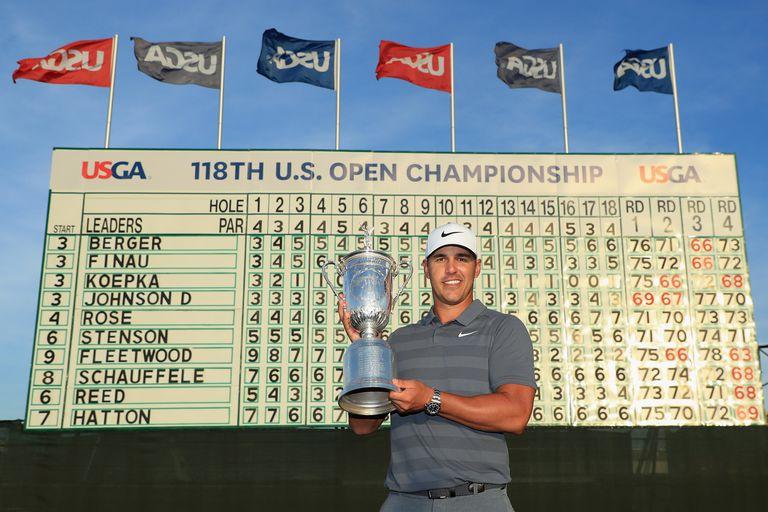 Brooks Koepka displays the trophy after winning the 2018 U.S. Open golf tournament.
