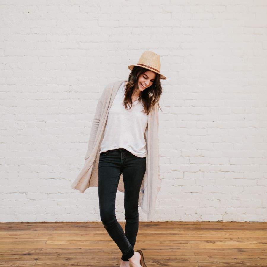 Woman in black jeans and t-shirt and long cardigan sweater