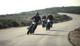 Three men wearing open face crash helmets and sunglasses riding cafe racer motorcycles along rural road.