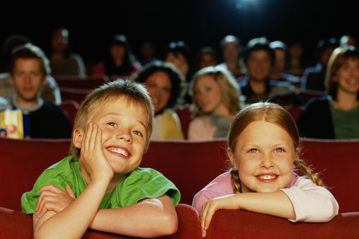 Boy and Girl (8-10) in Cinema, Smiling, Close-Up