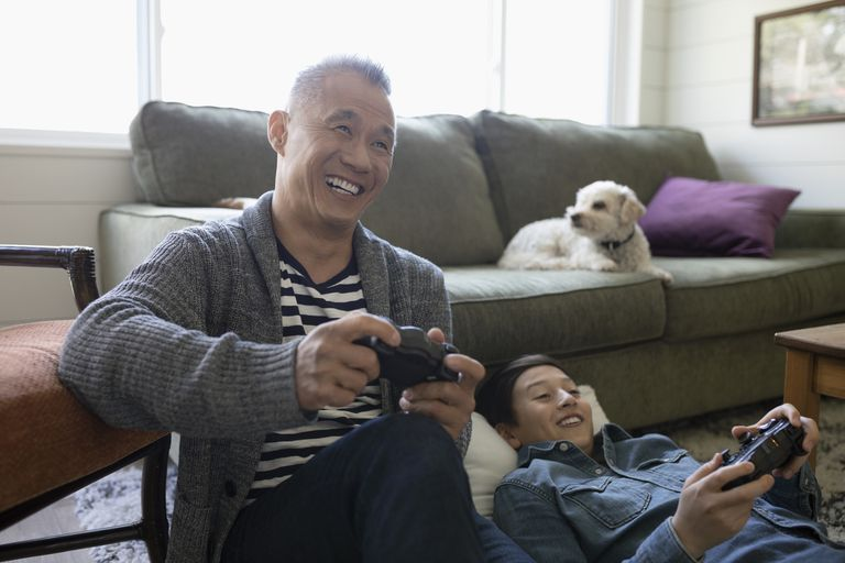 Father and son playing split-screen PS3 game in living room
