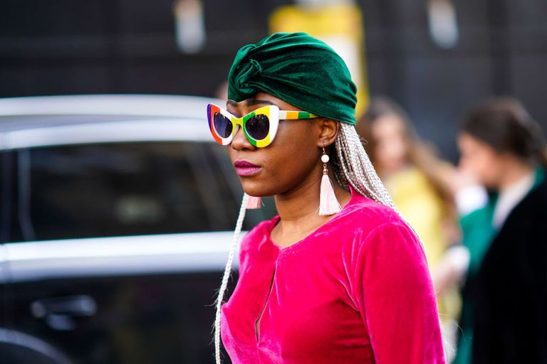 Street style woman wearing green turban plastic sunglasses and tassel earrings