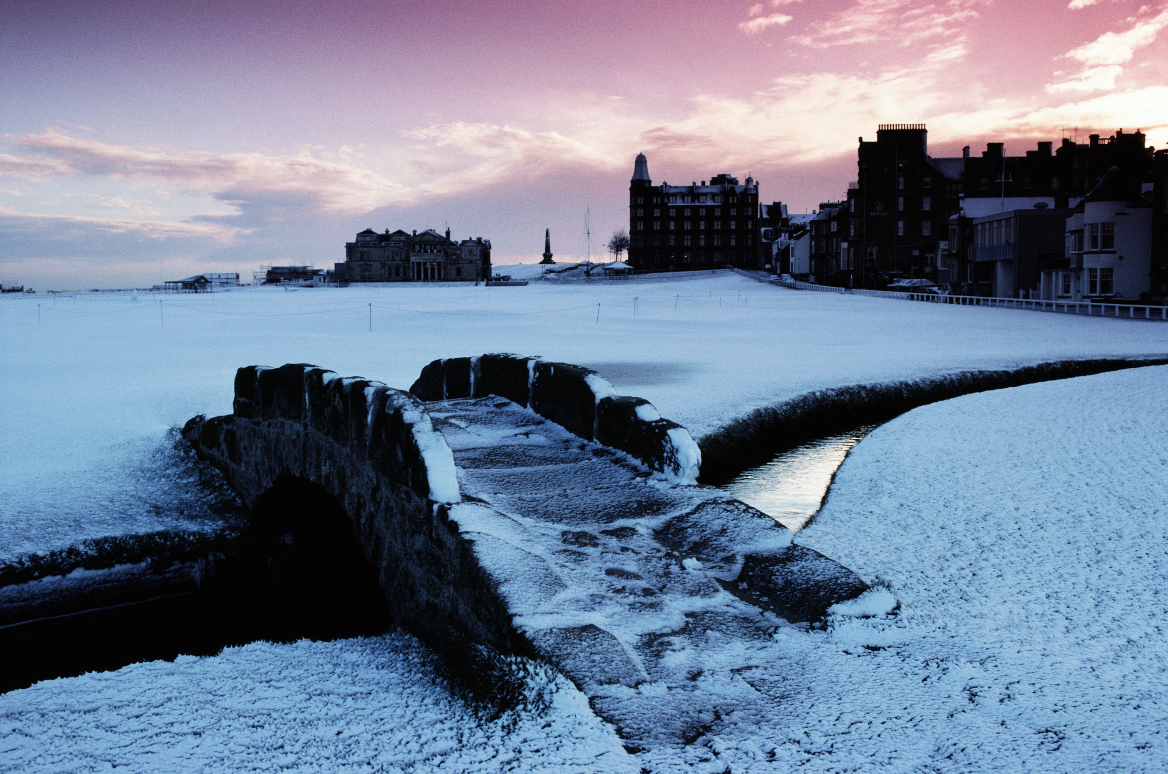 The Swilcan Bridge and the Old Course at St. Andrews under a light blanket of snow.