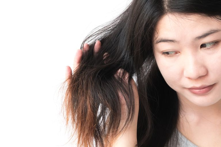 Close-Up Of Woman Looking At Hair Against White Background